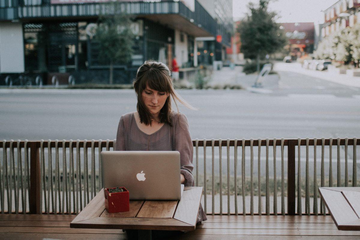 Ung kvinne sitter på kafe og ser på en laptop